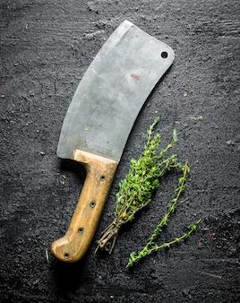 Tymianek z dużym nożem na czarnym rustykalnym stole.