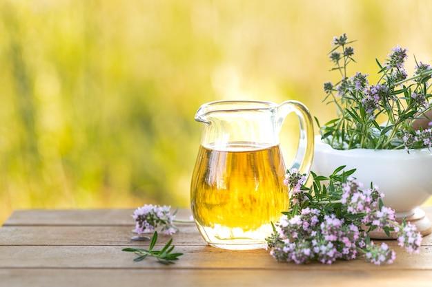 Tymiankowy olejek w szklanym dzbanku i gałąź świeża tymiankowa roślina z kwiatami na drewnianym tle. skopiuj miejsce