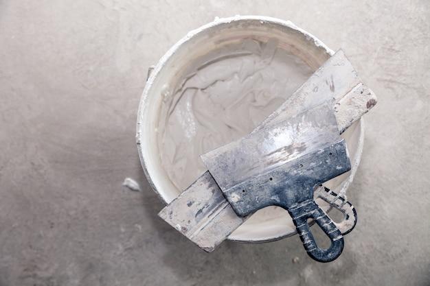 Tynk cementowy i zacieraczki w wiadrze budowlanym