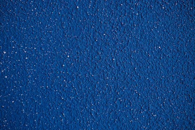 Tynk dekoracyjny i niebieska farba na ścianie. chropowata nierówna powierzchnia.