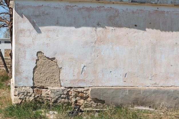 Tynk łuszczący się ceglany mur fundament budynku mieszkalnego stopniowo się zawala