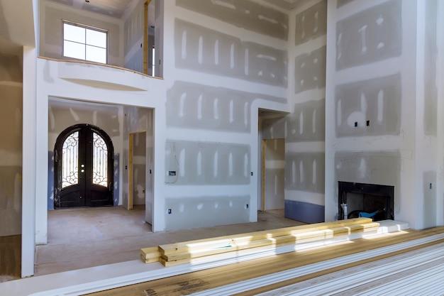 Tynkowanie płyt gipsowo-kartonowych nowego domu przemysłu na wykańczanie szpachli w pokoju ścian gipsowo-kartonowych z pomieszczeniem w budowie
