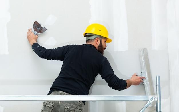 Tynkowanie ścian gipsowo-kartonowych pracownika.
