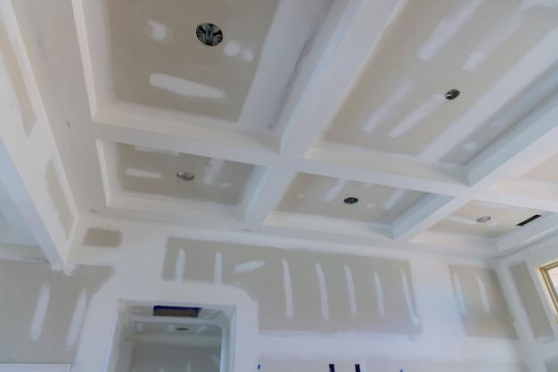 Tynkowanie szwów płyt gipsowo-kartonowych na ścianach i suficie nowego domu w trakcie procesu
