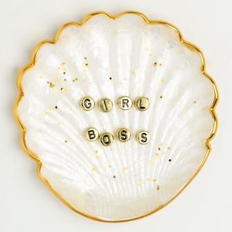 Typografia koralików szefa dziewczyny na złotej muszli