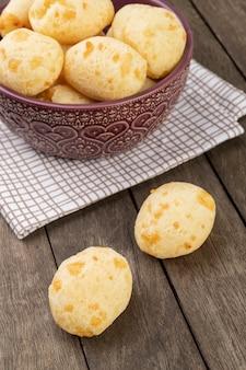 Typowa brazylijska bułka z serem w misce nad drewnianym stołem.