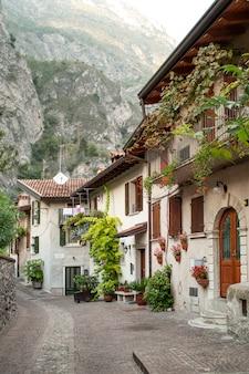 Typowa brukowana ulica we włoskiej wiosce z fasadami ozdobionymi roślinami doniczkowymi i kwiatami