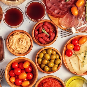 Typowa hiszpańska koncepcja tapas. koncept obejmuje plasterki jamona, chorizo, kiełbasę, miski z oliwkami, pomidory, anchois, puree z ciecierzycy, ser.
