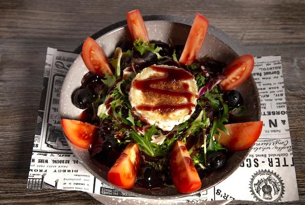 Typowa hiszpańska koźlia serowa sałatka na drewnianym tle. pojedyncze zdjęcie