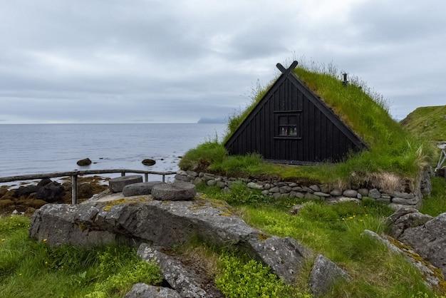 Typowa islandzka wioska rybacka z domami pokrytymi trawą i stojakami do suszenia ryb