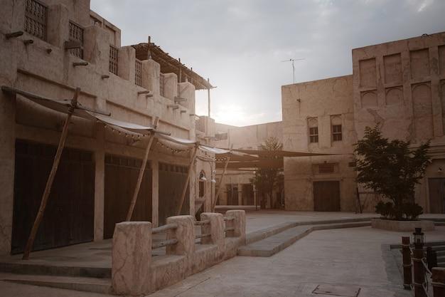 Typowa lokalna architektura w al seef w dubaju zea o zachodzie słońca, tradycyjne stare arabskie miasto - wioska targowa