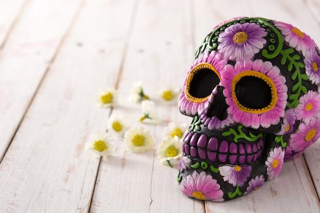 Typowa meksykańska czaszka malowana na białym drewnianym stole.