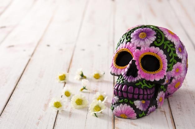 Typowa meksykańska czaszka z kwiatami malowanymi na drewnianym stole.