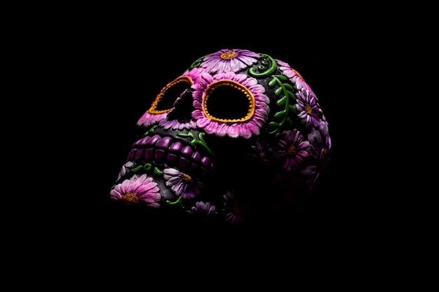 Typowa meksykańska czaszka z kwiatami namalowanymi na czarnym tle. dia de los muertos.