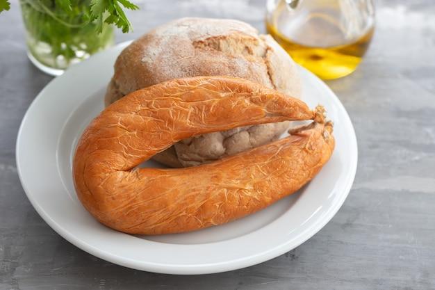 Typowa portugalska kiełbasa farinheira z chlebem na białym talerzu na ceramice