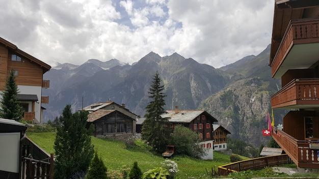 Typowa szwajcarska wioska z drewnianymi domami na szczycie zbocza surowych gór alpejskich.