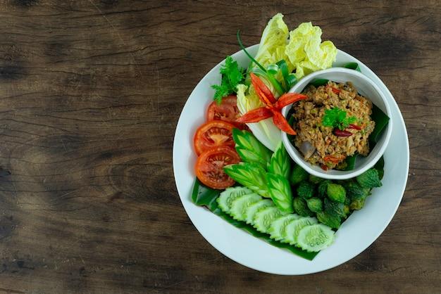 Typowa tajlandzka pasta chili z suma z grilla na białym talerzu na drewnianym tle widok z góry