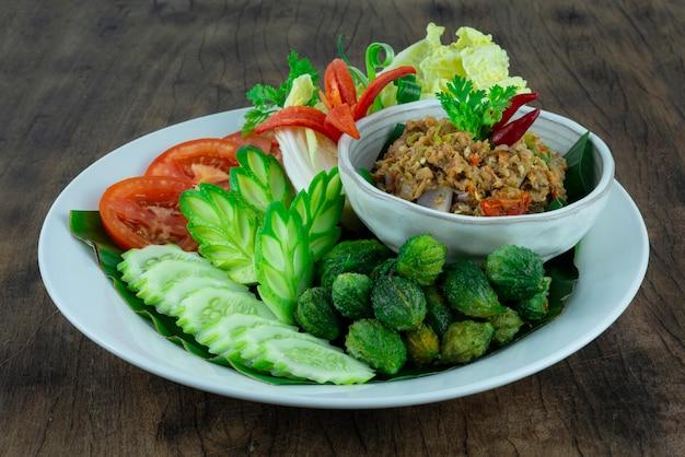Typowa tajlandzka pasta chili z suma z grilla na białym talerzu na drewnianym tle