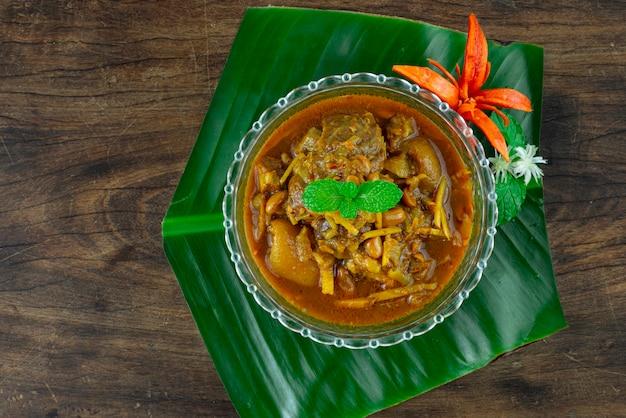 Typowa tajlandzka wieprzowina hunglay z przyprawą masala curry w misce nad dużym liściem na drewnianym tle