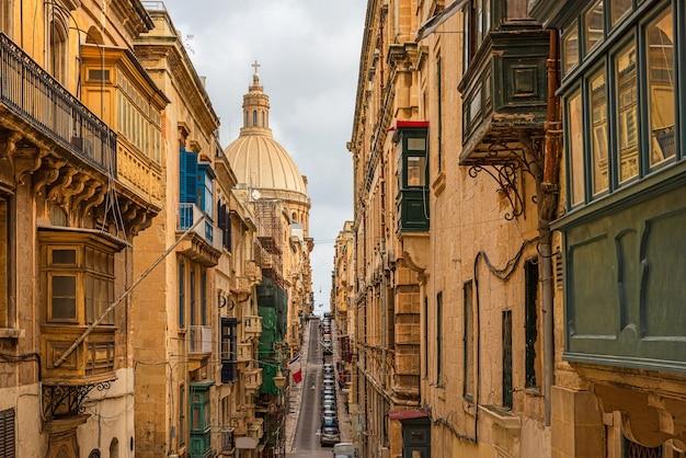 Typowa wąska ulica valletty z kopułą katedry, żółtymi budynkami i kolorowymi balkonami, malta, europa