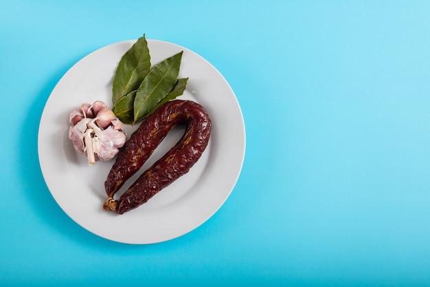 Typowa wędzona kiełbasa portugalska chourico na talerzu na niebieskim tle