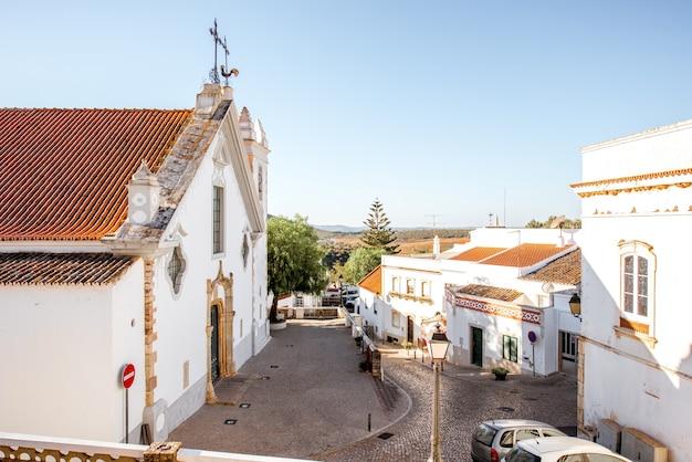 Typowa wioska z białym starym kościołem podczas wschodu słońca na południu portugalii