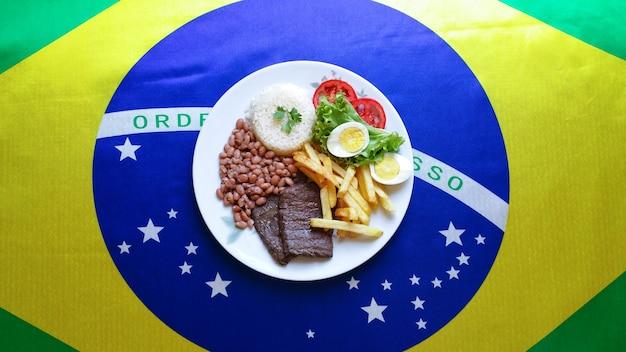Typowe brazylijskie danie z brazylijską flagą na powierzchni.