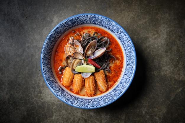 Typowe gorące danie ramenowe z bulionem rybnym w misce z czarnym makaronem, kalmarami, chilli, małżami.