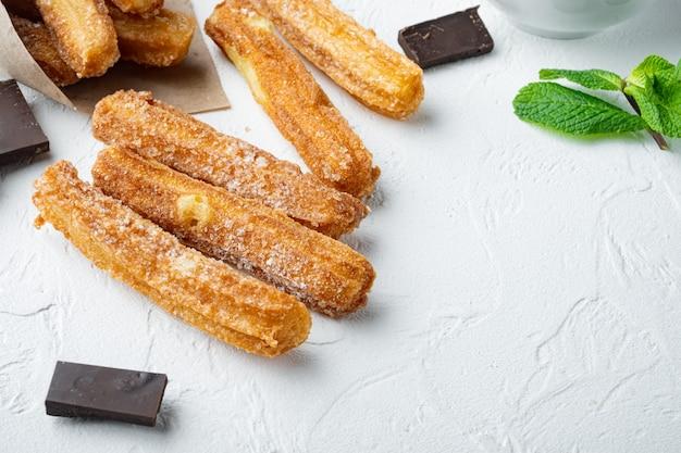 Typowe hiszpańskie churros z przekąskami, ciasto ze smażonego ciasta podawane zwykle z zestawem gorących sosów czekoladowo-karmelowych, na białym stole, copyspace