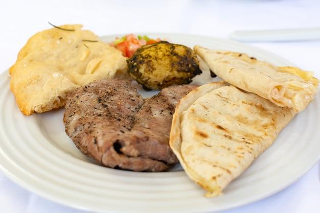Typowe meksykańskie jedzenie talerz z mięsem i tacos na stole z białym obrusem