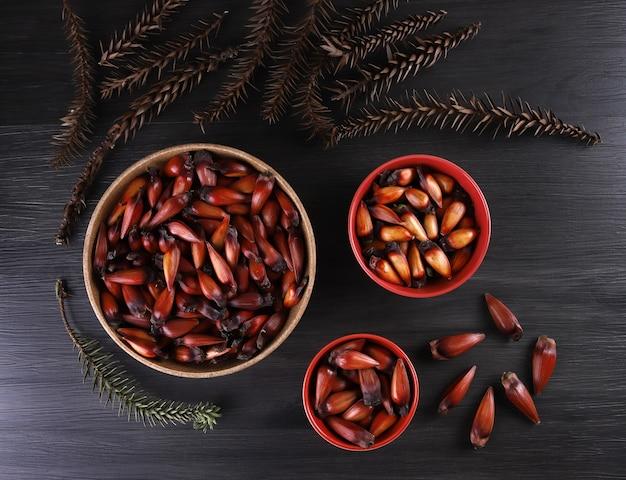 Typowe nasiona araukarii używane jako przyprawa w kuchni brazylijskiej zimą. brazylijskie orzechy pinion w brązowej i czerwonej drewnianej misce na szarym drewnianym tle.