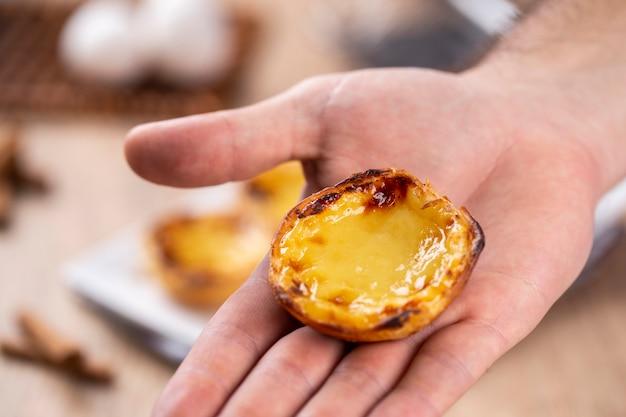 Typowe portugalskie ciasta z kremem. tradycyjne ciasto portugalskie. trzymając przez szefa kuchni.
