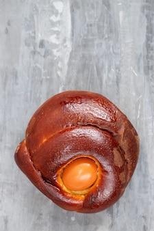 Typowe portugalskie ciasto wielkanocne folar z jajkiem na ceramicznej powierzchni
