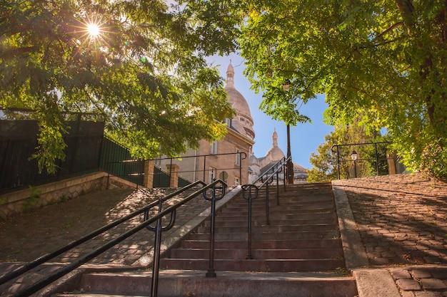 Typowe słoneczne schody montmartre do sacre-coeur rano i światło słoneczne wpadające przez drzewa, dzielnica montmartre w paryżu, francja