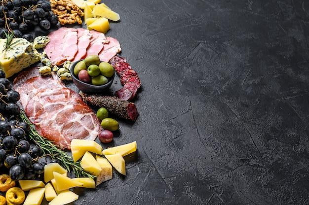 Typowe włoskie antipasto z prosciutto, szynką, serem i oliwkami. czarne tło. widok z góry. miejsce na tekst