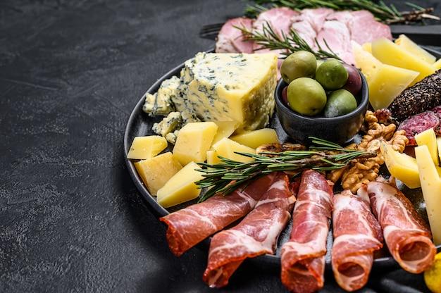 Typowe włoskie antipasto z prosciutto, szynką, serem i oliwkami.
