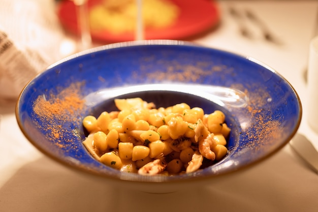 Typowe włoskie danie gnocchi z owocami morza w niebieskiej misce