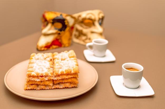 Typowe włoskie placki karnawałowe (chiacchiere di carnevale) posypane proszkiem.