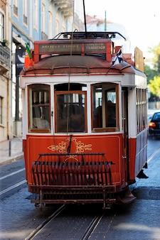 Typowy czerwony tramwaj w starej lizbońskiej ulicy