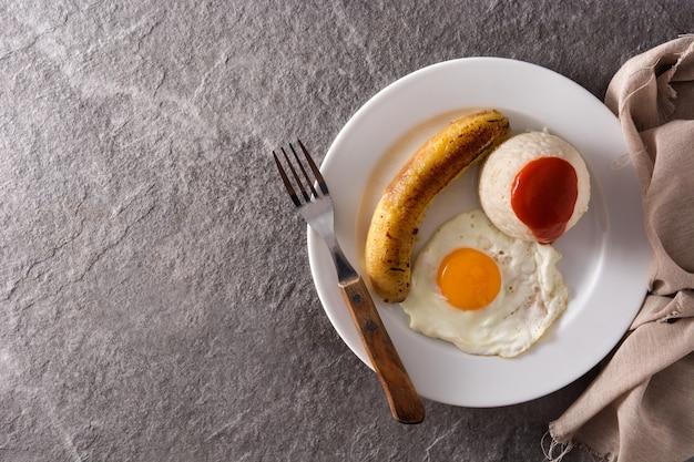 Typowy kubański ryż ze smażonym bananem i jajkiem sadzonym na talerzu na szarej powierzchni