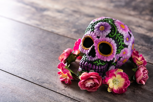 Typowy meksykański diadem czaszki i kwiaty na drewnianym stole. dia de los muertos.