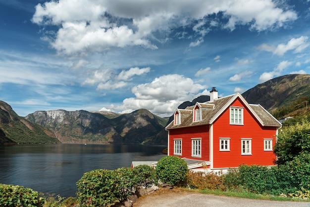Typowy norweski czerwony dom w tle malowniczego fiordu. piękny krajobraz norwegii z czerwonym domem i atmosferycznym niebem.