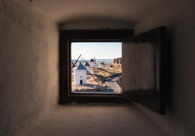 Typowy stary biały wiatrak i średniowieczny zamek w hiszpanii widziany z okna wewnątrz młyna