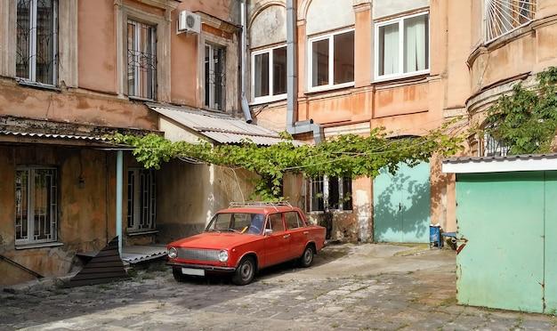 Typowy stary radziecki dziedziniec z czerwonym samochodem