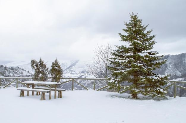 Typowy zimowy widok bożonarodzeniowy na górzysty teren ze stołem i ławką z drewna jodłowego, wszystko pokryte grubą warstwą śniegu