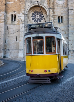 Typowy żółty tramwaj jadący w górę dzielnicy alfama przed katedrą w lizbonie portugalia
