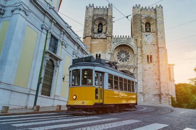 Typowy żółty tramwaj jadący w górę dzielnicy alfama przed katedrą w lizbonie - portugalia