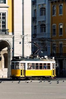 Typowy żółty tramwaj na starej ulicy w lizbonie
