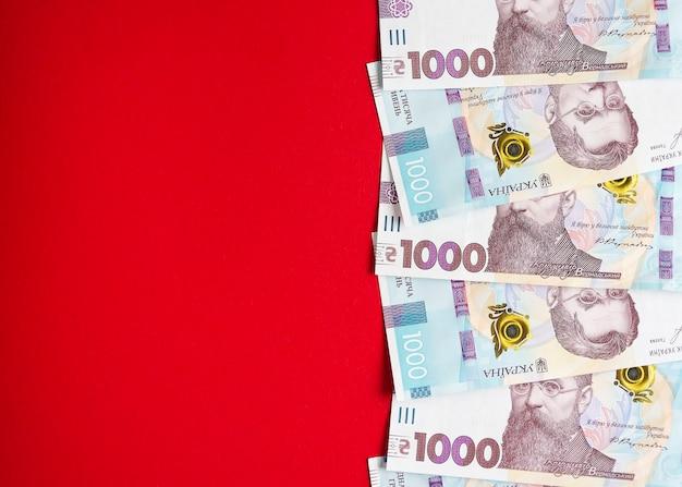 Tysiąc banknotów hrywny ukraińskiej na czerwonym tle 2