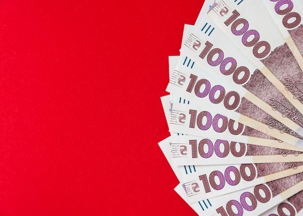 Tysiąc banknotów hrywny ukraińskiej na czerwonym tle 6